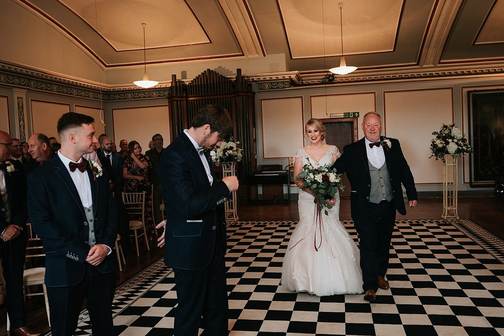 bride walks down the aisle at wedding at st annes palace