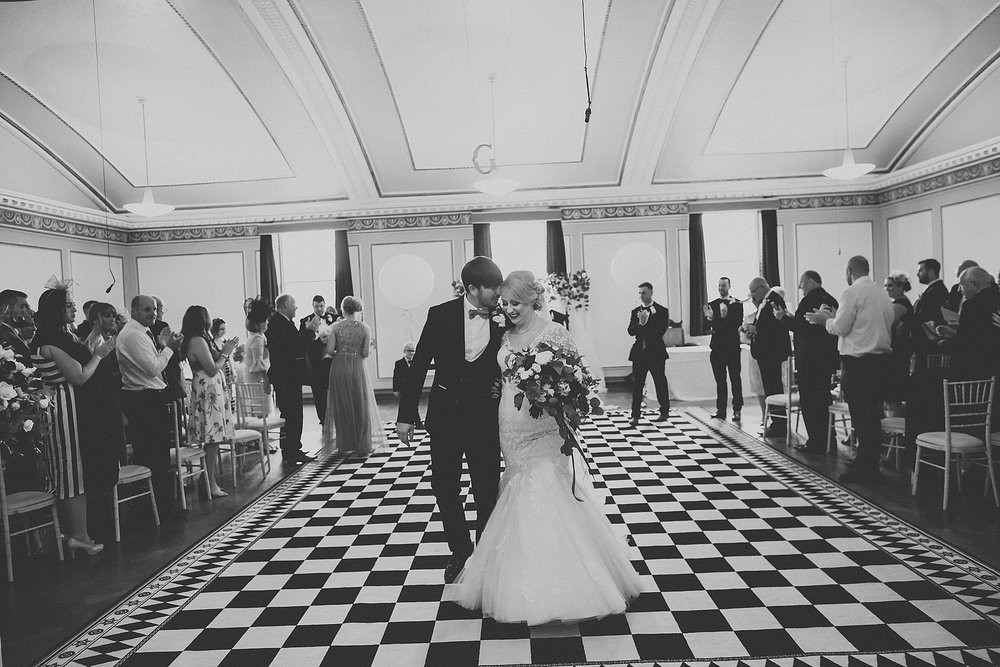 wedding couple walk out of ceremony room at st annes palace