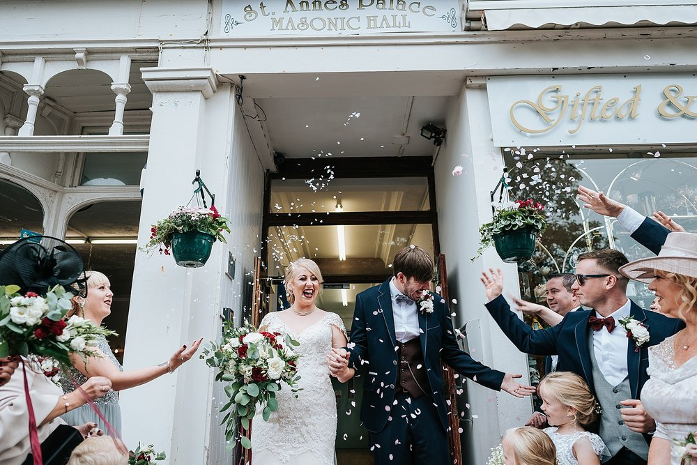 bride and groom having confetti thrown at them outside vintage wedding venue in lancashire
