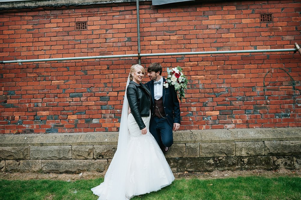 cool bride and groom in front of red brick in ashton park, st annes
