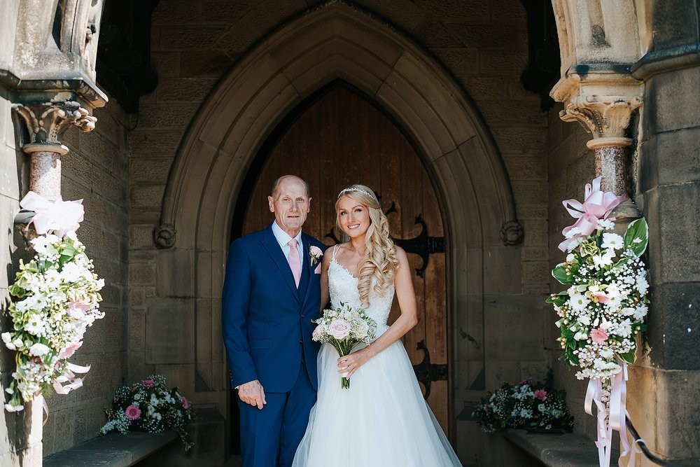 bride with father at all saints church in preston