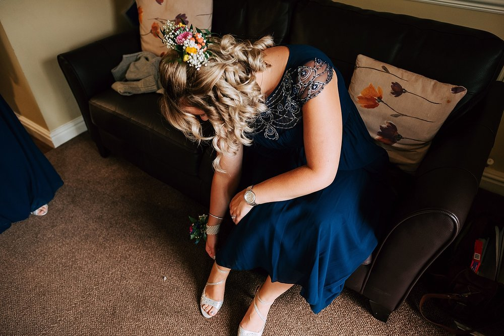 bridesmaid puts shoes on for summer wedding