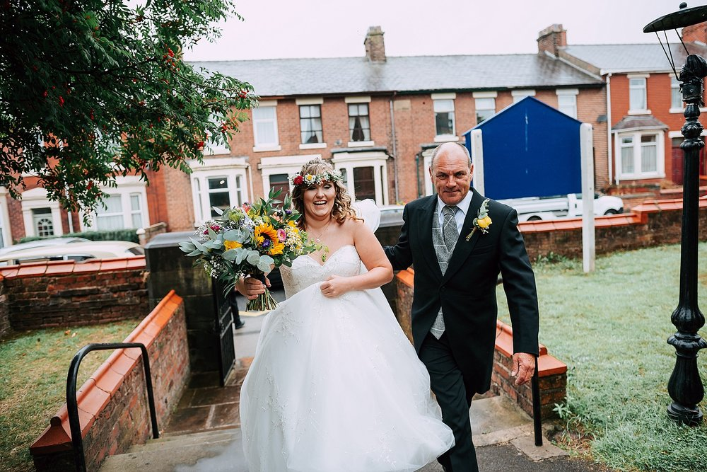 bride and her dad walk up path at christ church wesham