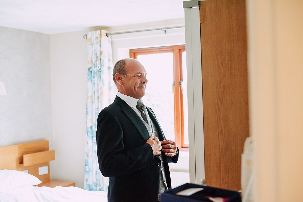 father of the groom gets ready at wedding