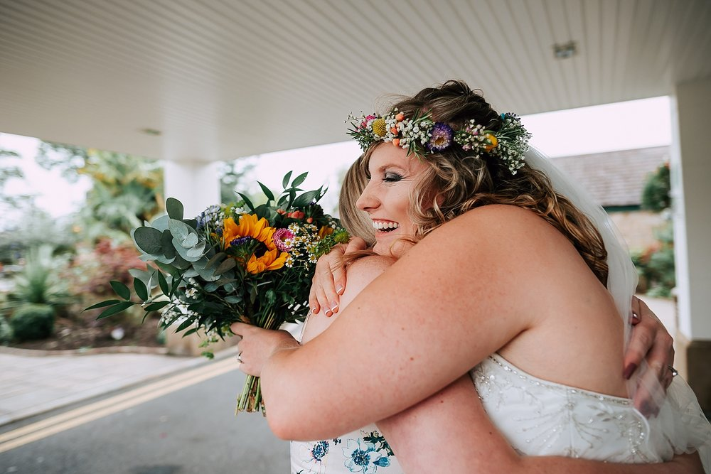 bride greeting a guest at a summer wedding