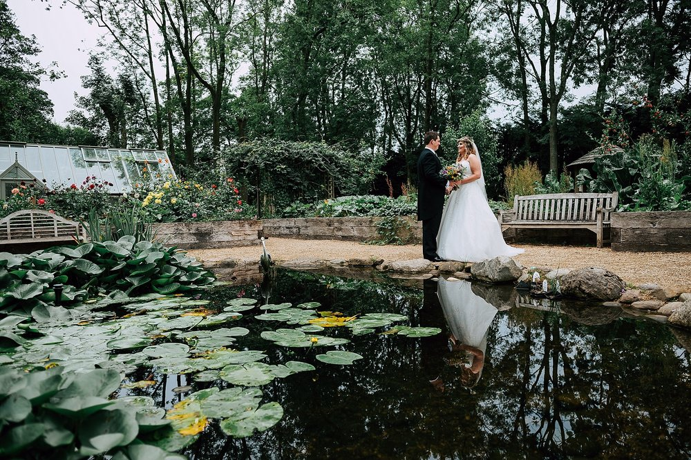 bride and groom next to pond in the village garden