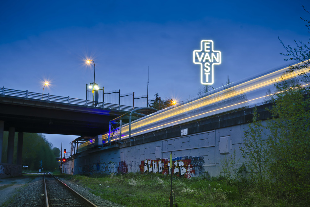 East Van sign lit up at night with the sky train passing by at VCC Clark Station.  Love graffiti next to the tracks.
