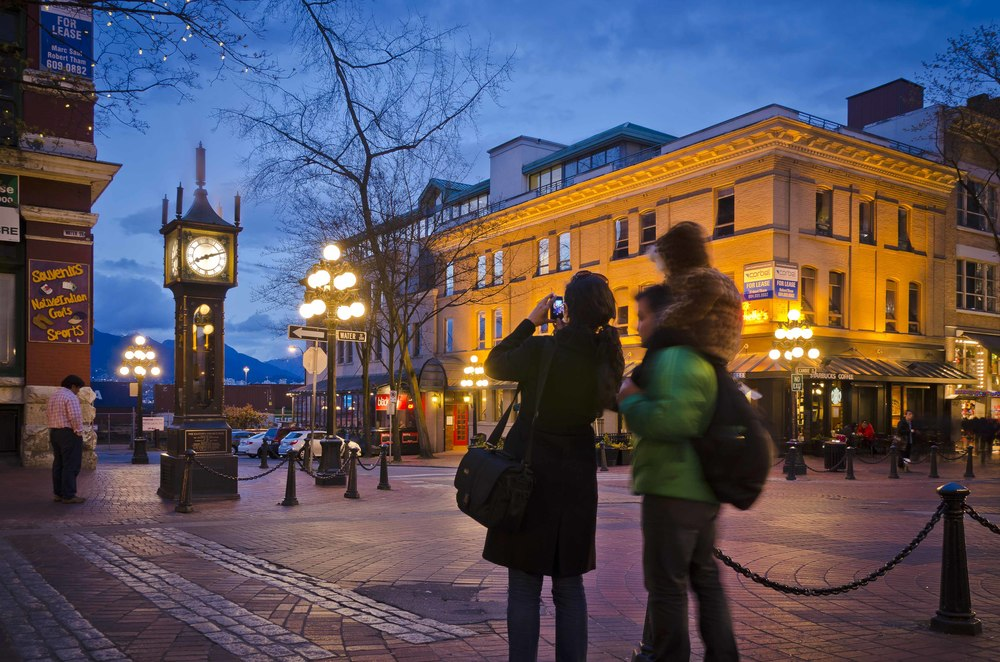 Family takes a photo in front of the Gastown Steam Clock, with the North Shore Mountains behind.