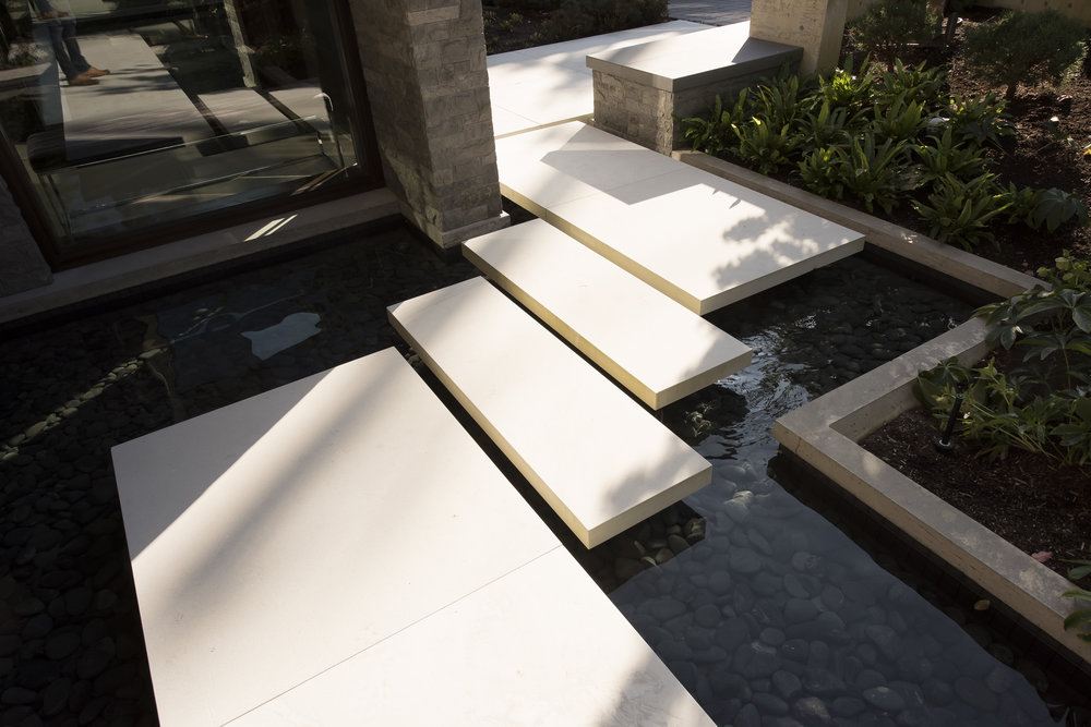 floating concrete stepping stone pathway over water feature
