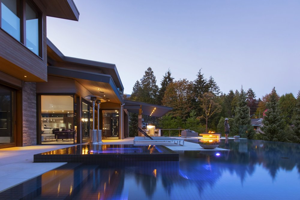 Infinity pool and patio at modern Vancouver home dusk