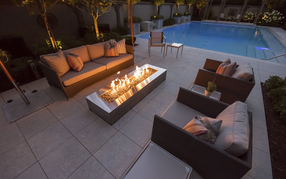 Outdoor fireplace poolside at Vancouver home and garden