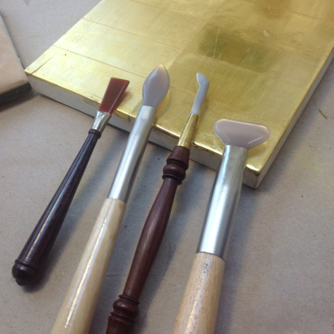 Different shapes of burnishing tools, which are typically made of agate mounted on a handle.