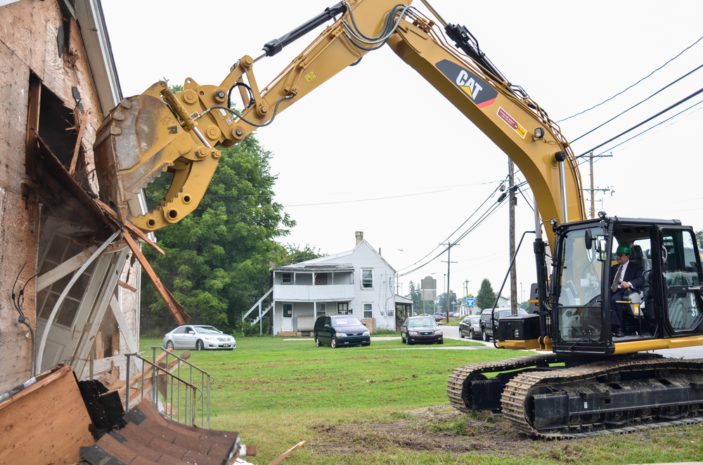 New Castle Executive Tom Gordon using a back hoe to demolish a abandoned home in Middletown, de.