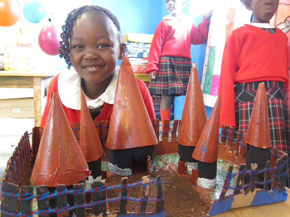 Movin, kindergarten, behind a model of a traditional Luhya village
