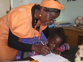Ashley Adhiambo signs her contract along with Headmistress Okumu.
