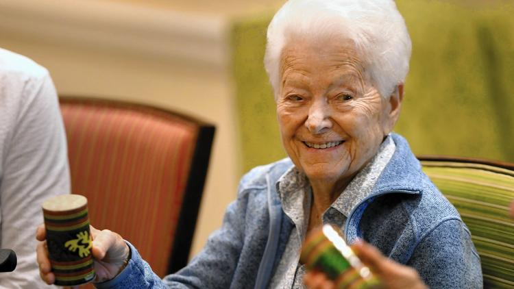 Lake Forest Place resident Lu Zobel plays a shaker along with the music at a special performance at the retirement community by members of the Lake Forest Symphony. (Brian O'Mahoney / Pioneer Press)