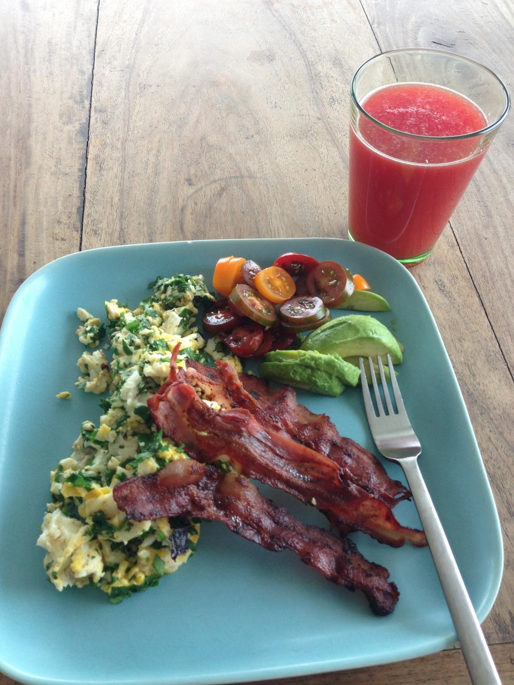 Frukost - äggröra med persilja, bacon, avokado och sköna blandade tomater.  Till detta vattenmelon juice