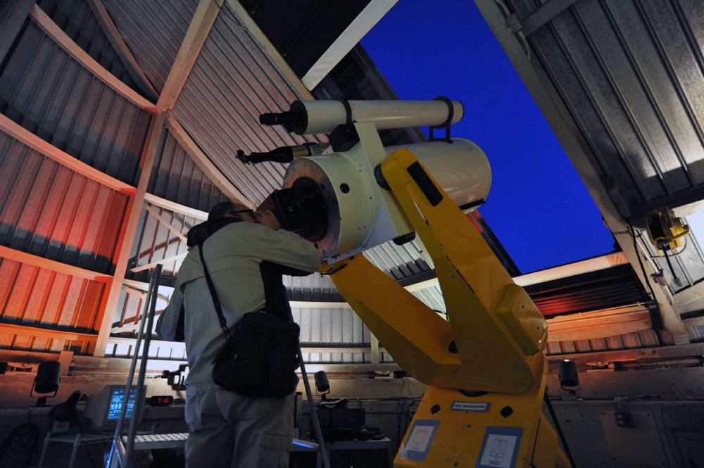 Guest peers through the Doane Observatory to catch a glimpse of the night sky.