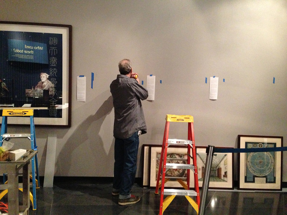 Adler staff preps installation hardware for works on paper wall.