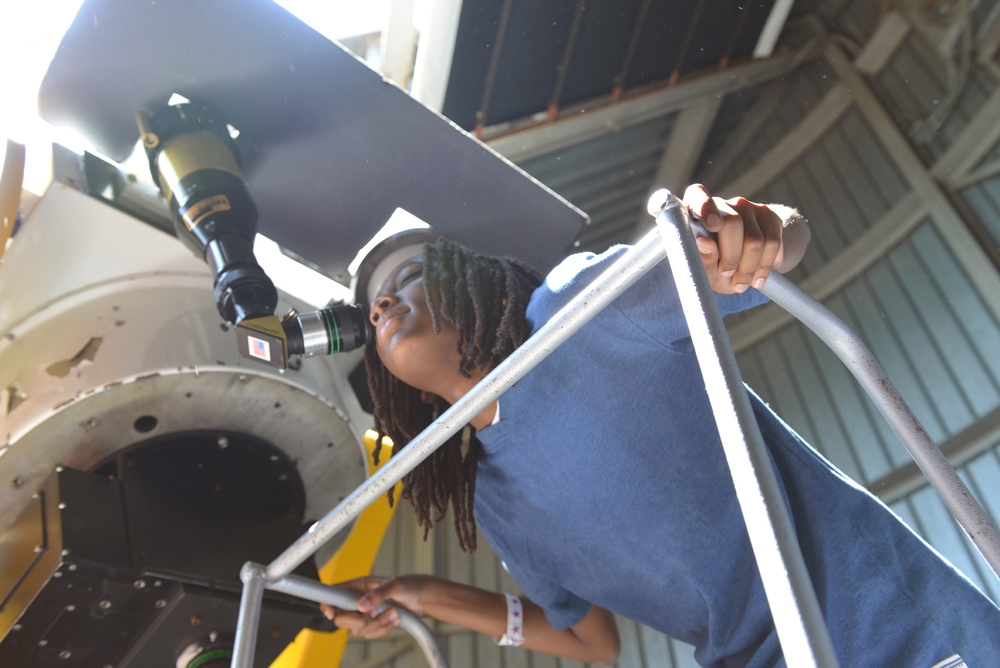 Teen looking through the Doane Observatory telescope