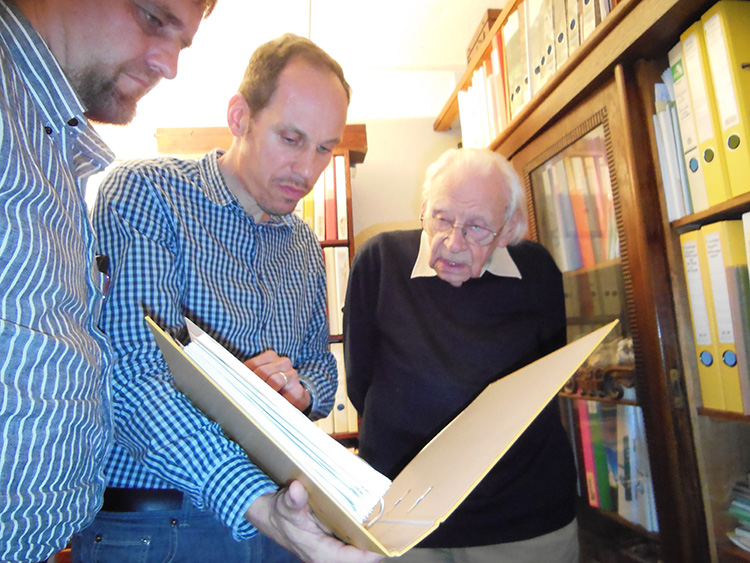 (Left to Right) Dr. Marvin Bolt, Michael Korey, and Rolf Reikher examine historic documents.