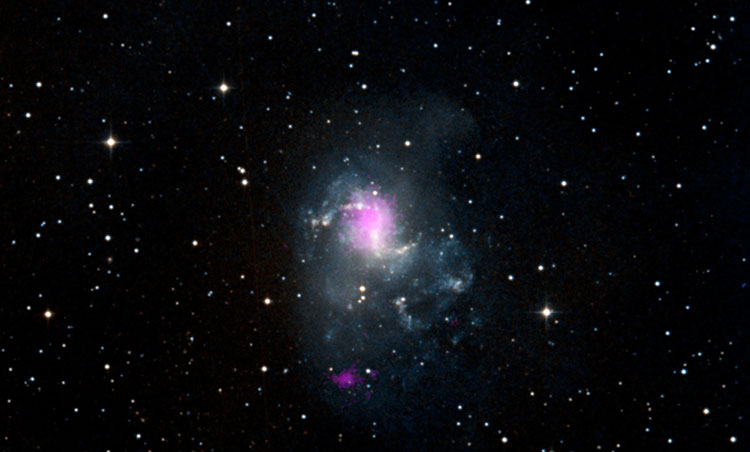 The magenta spots in this image show two black holes in the spiral galaxy called NGC 1313, or the Topsy Turvy galaxy. Both black holes belong to a class called ultraluminous X-ray sources, or ULXs. Image Credit: NASA/JPL-Caltech/IRAP