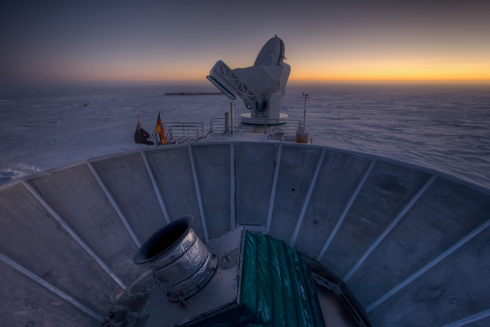 The BICEP2 telescope in the foreground, with the South Pole Telescope in the background. The Sun is setting for the 6 months of darkness during the South Pole winter.