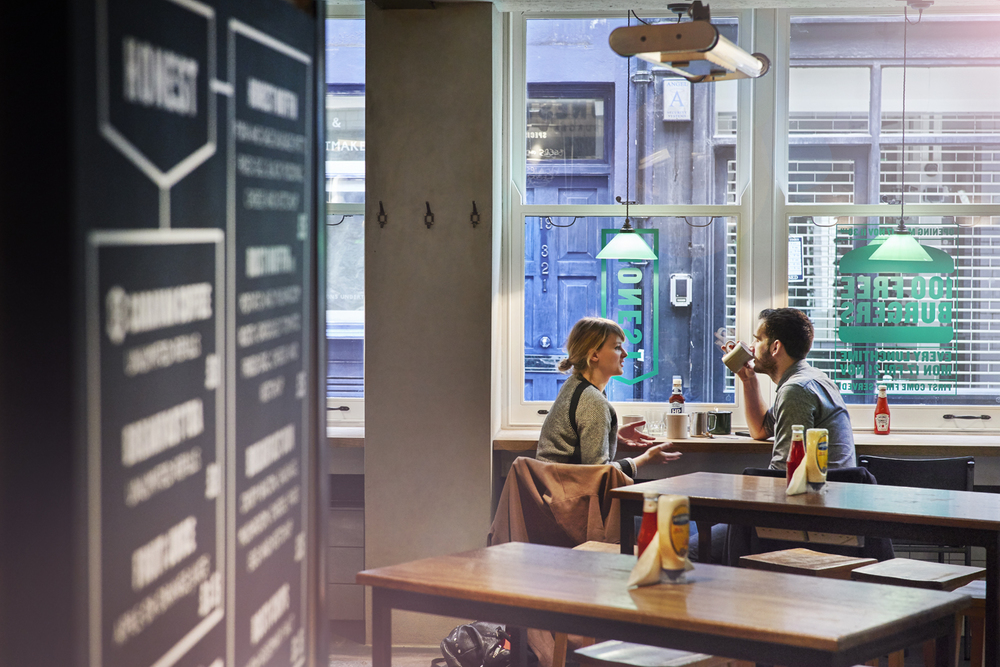 Couple drinking coffee and having breakfast at Honest Burger's new location in Liverpool Street. Imagery and Photography by London based still life and food photographer Scott Grummett.