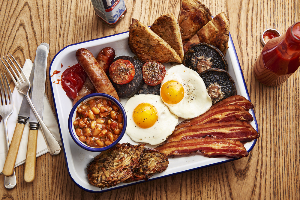 Honest Burgers full english breakfast platter featuring fried eggs, streaky bacon from the ginger pig, cumberland sausages, baked beans, mushroom roti, black pudding, roast tomatoes, portobello mushrooms, guinness eggy bread french toast, ketchup and hp sauce. photographed by london food and still life photographer and director scott grummett