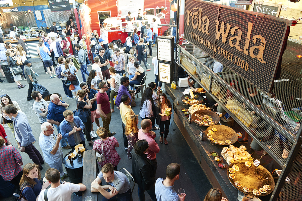 Street food photography from street feast in dalston yard, shoreditch dinerama and lewisham model market. Natural daylight lifestyle shots from photographer and director scott grummett of street food and drink in london used for advertising press pr packaging and editorial. lifestyle friends role wall indian chapati poppadoms sliders curry