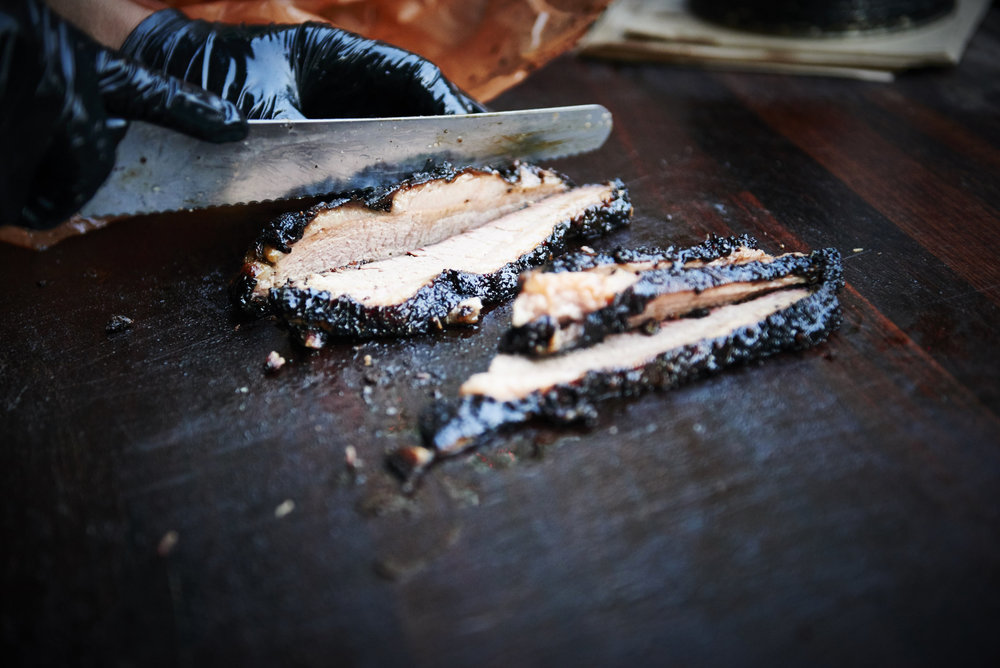 Street food photography from street feast in dalston yard, shoreditch dinerama and lewisham model market. Natural daylight lifestyle shots from photographer and director scott grummett of street food and drink in london used for advertising press pr packaging and editorial. smokestack smoke stay bbq barbecue vendor lather juicy bbq. selling market buns toasted tray food smoky delicous carving slices