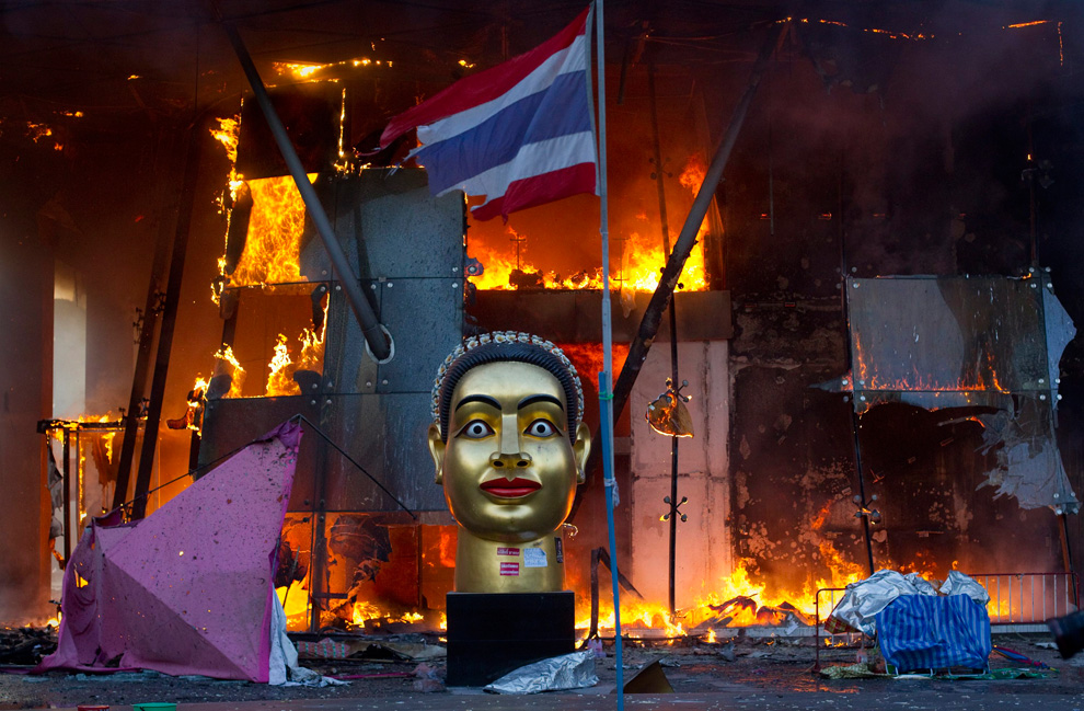A statue and a torn Thai national flag remain in front of Bangkok's Central World shopping mall, which was gutted by fire after army soldiers advanced towards an encampment of thousands of Red Shirt protesters, May 19, 2010. (REUTERS/Adrees Latif)    via  boston.com