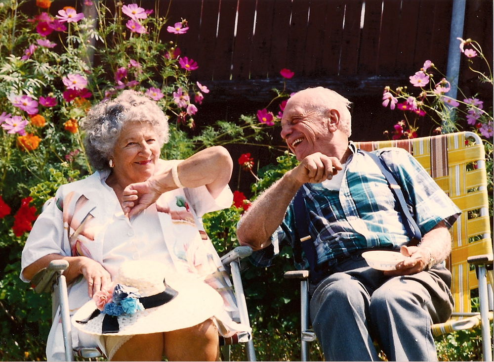 I love this picture. These are the very aluminum fold out chairs I was talking about. Nothing fancy for these folks, just the important stuff. Look at his beautiful garden behind them.