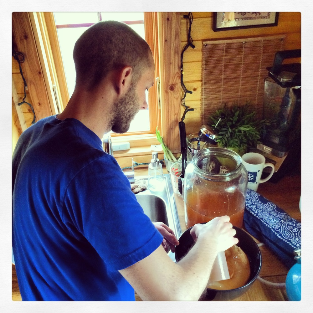 Chris making a fresh batch of home brewed Kombucha! He has separated the mother from the jar and coving it in some of the liquid.
