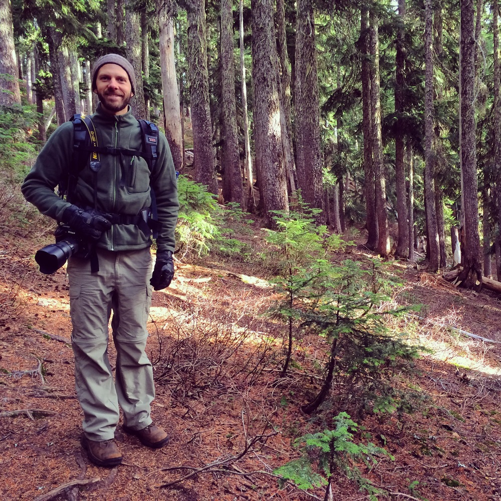 Christopher posing for a picture in the woods. Got his camera ready to capture some of the beautiful surroundings.