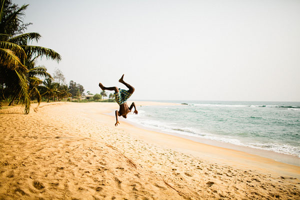 Liberia boy jumping in sand African Africa boy
