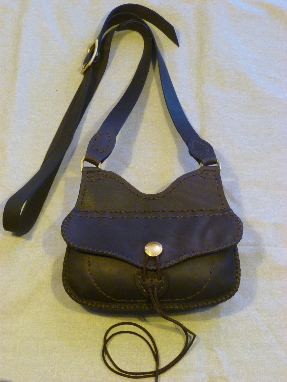 "Small Hunting Bag with no side pocket:  Two inside pockets and an outside pocket on the back of the bag with a flap.  Lanyard closure with brass button catch.  Size: 9.5"" x 4.5"" x 2.5""  Price: $70.00  Inventory Tag: GB-7-SMB"