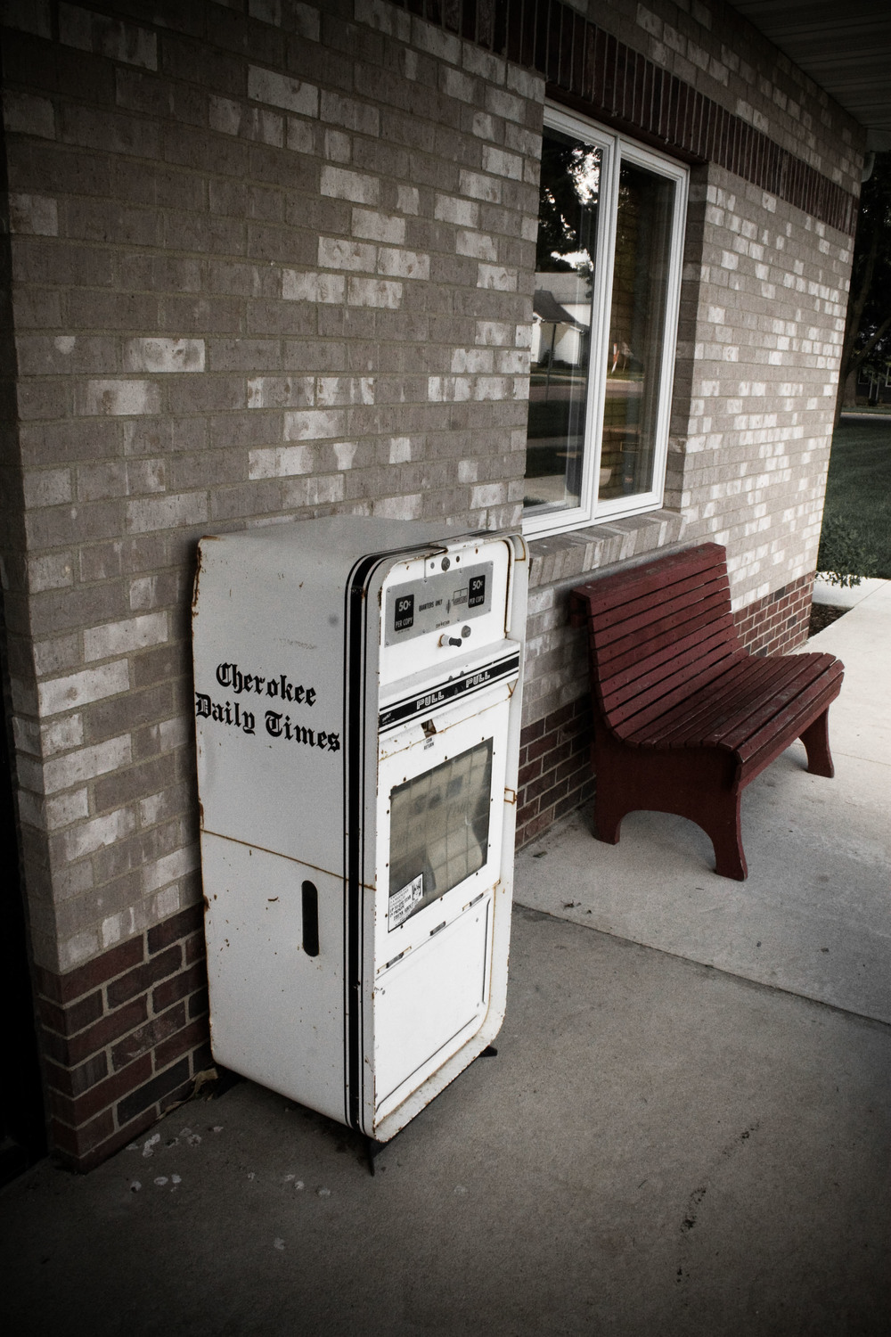 Newspaper stand by a bench