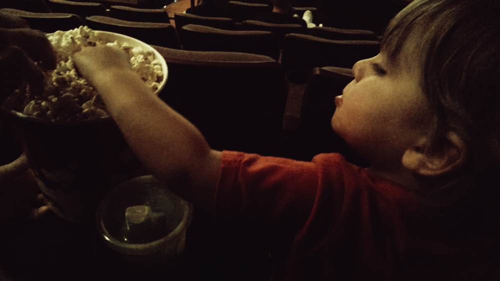 Eating popcorn at his first movie!