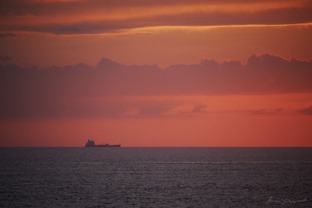 A ship moves across the horizon in the distance at Sunset over the Irish Sea. In the middle of the Irish sea, on the Ferry from Wales to Dublin, as the sun sets on the horizon, and the sky turns a deep red.
