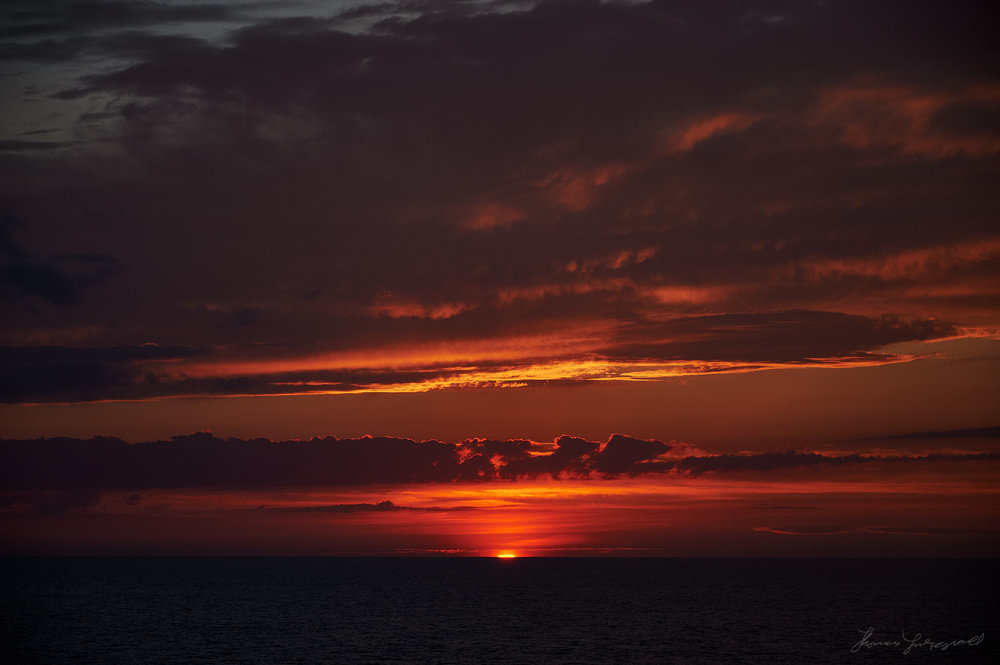 Sunset over the Irish Sea. In the middle of the Irish sea, on the Ferry from Wales to Dublin, as the sun sets on the horizon, and the sky turns a deep red.