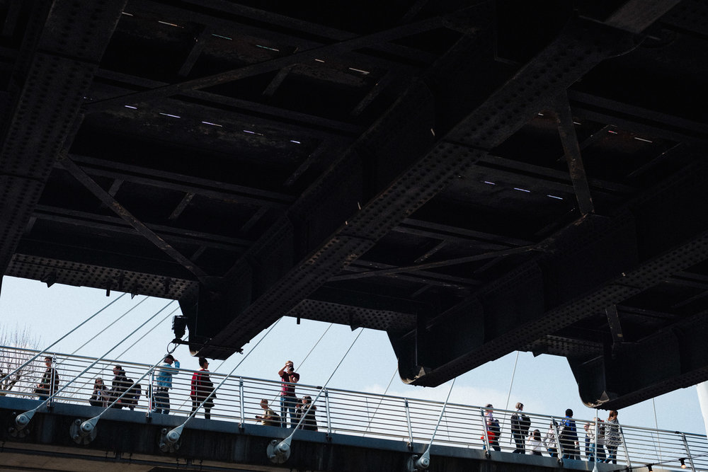 Photographer on a bridge overlooking the southbank walkway in London
