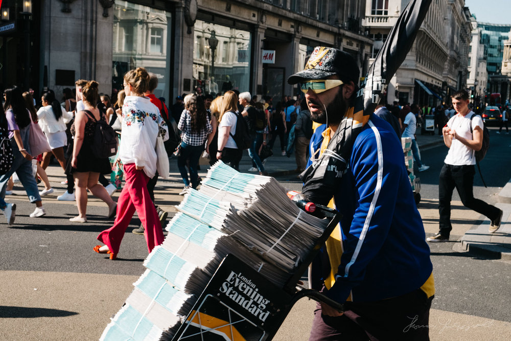 Man carries newspapers across the busy Oxford Circus junction in London