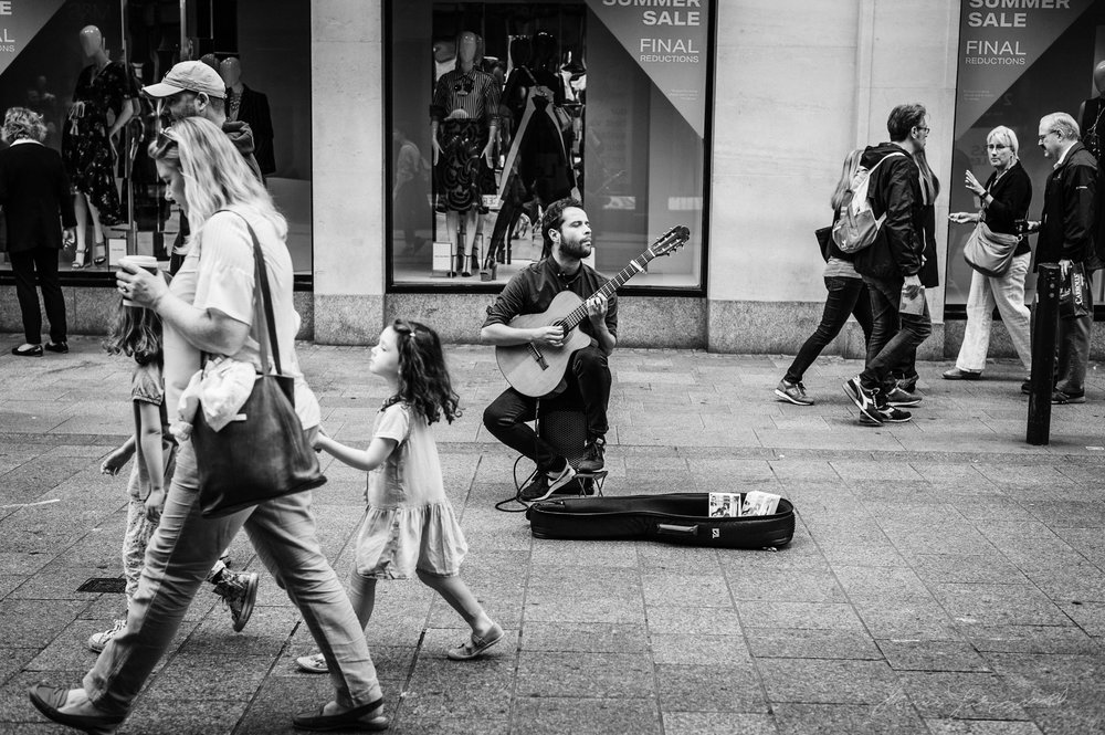 man playing guitar on Dublin's grafton street