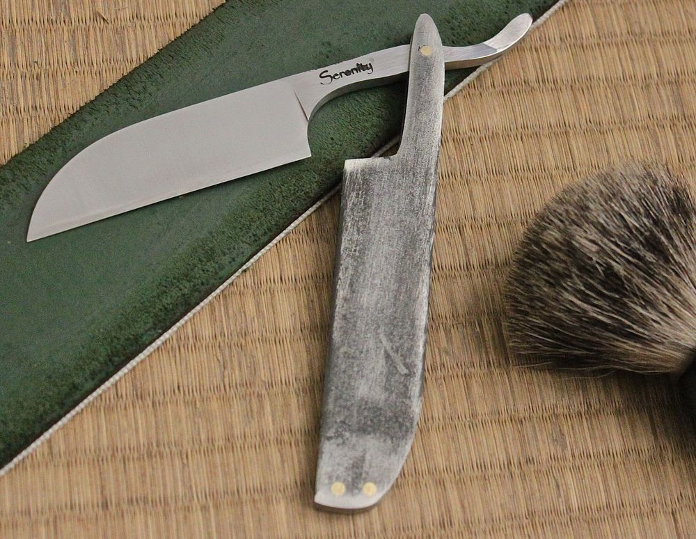 A 13C26 razor blade with textured 440C handle.