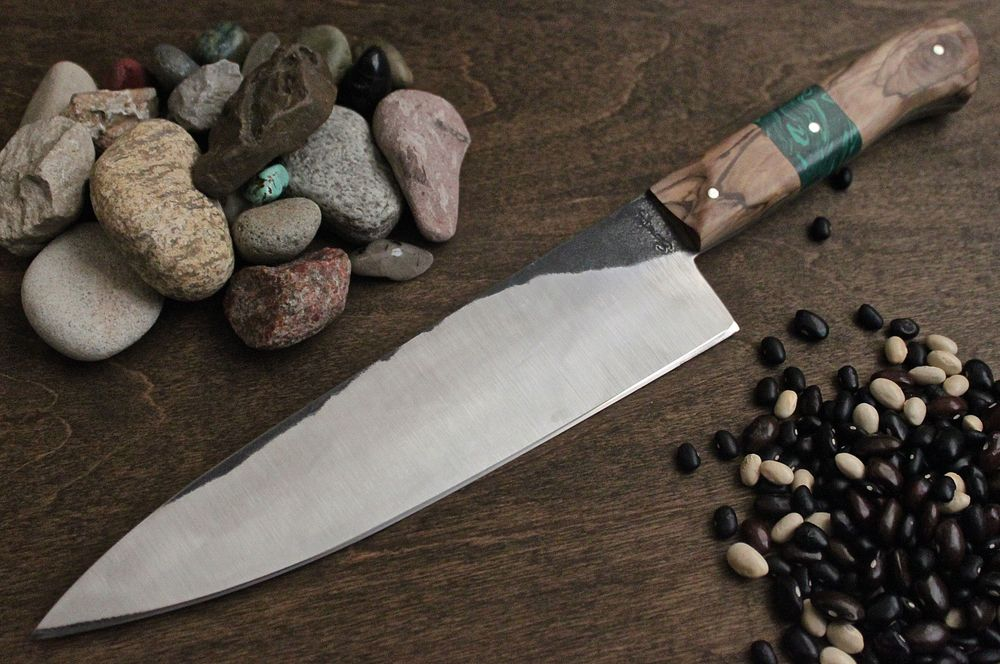 This is a barter Knife. Custom Gyuto malachite interruption in olive wood. An artist in Seattle traded me a HUGE print of an amazing photo.
