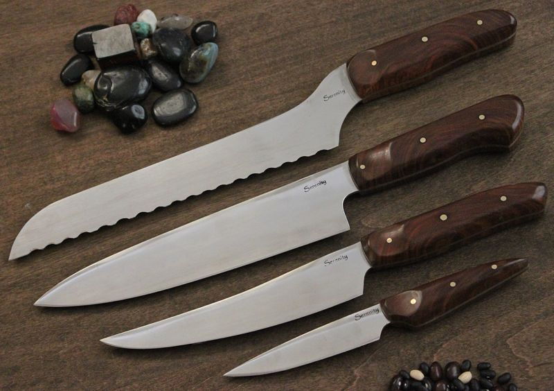 "A set of kitchen knives, Bread Gyuto, Slicer or boning, and eviscerator paring knife,  in Lignum Vitae and 1/8"" brass pins."