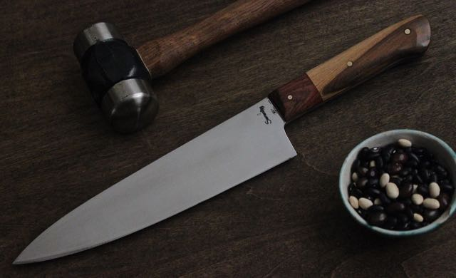 A gyuto with a wood bolster on a wood handle.