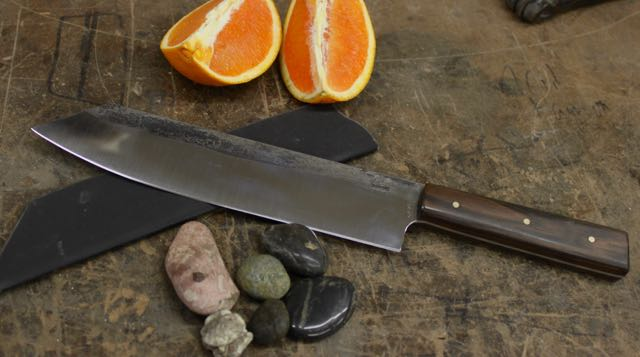 "Gyuto: Kiritsuki point with rectangular shaped handle in  CPM154 Stainless blade, Natural Masacar Ebony handle. Buffed Forge Finish on the blade. 3 - 1/8"" brass pins. Custom Kydex knife transporter is included.              Blade Length: 7 1/4""                                         Handle Length: 4 3/8""              Overall Length: 12 1/2""              Blade Depth: 1 5/8""                                           Blade Thickness: .105""             Handle Thickness: .776"""
