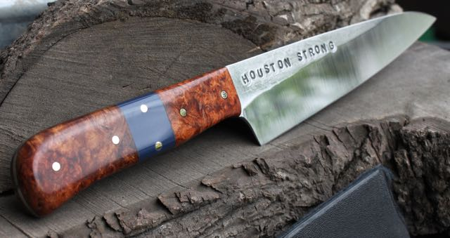 """Kitchen Utility - Petty/Honesuki knife: 52100 Complex High Carbon steel blade, Stabilized amboyna burl handle with blue kirinite interuption, buffed forge Finish. Brass 1/8"""" pinss with 1 mosaic pin in front. Custom Kydex knife transporter is included. Blade Length: 5 3/4"""" Handle Length: 4 1/2"""" Overall Length: 10 1/2""""Handle Depth: 7/8"""" Blade Depth: 1 1/2""""Blade Thickness: .100"""" Handle Thickness: .732"""" tappered to .357""""    Heel to handle: 5/8""""  This Knife was started the week after Hurricane Harvey devastated much of the Gulf Coast region of Texas. It was inspired by all who helped neighbors, friends, strangers and loved ones. We choose High Carbon steel for this knife as it will patina with use, staining, scaring and becoming more beautiful, as it does what it does.A portion of the proceeds of the sale of this knife will go towards the ongoing Hurricane Harvey Relief."""